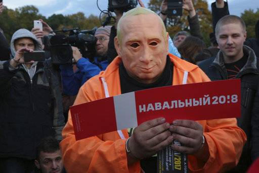 A protester wearing a mask depicting Russian President Vladimir Putin, holds a poster reading Navalny 2018 during a rally in St. Petersburg, Russia, Saturday, Oct. 7, 2017. In a challenge to President Vladimir Putin on his 65th birthday, protesters rallied across Russia on Saturday, heeding opposition leader Alexei Navalny's call to pressure authorities into letting him enter the presidential race.