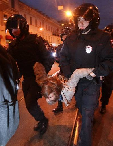 Riot police officers detain a protester during a rally in St. Petersburg, Russia, Saturday, Oct. 7, 2017. In a challenge to President Vladimir Putin on his 65th birthday, protesters rallied across Russia on Saturday, heeding opposition leader Alexei Navalny's call to pressure authorities into letting him enter the presidential race.