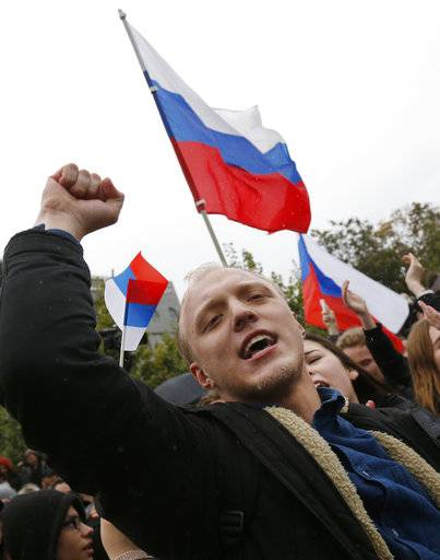 A demonstrator clenches his fist as other wave Russian flags during a rally in Moscow, Russia, Saturday, Oct. 7, 2017. Opposition leader Alexei Navalny has worked to organize protests in support of his presidential bid across Russia on Saturday, President Vladimir Putin's birthday.