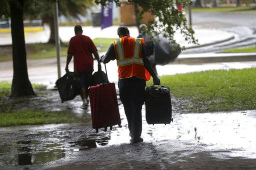 A sanitation employee, foreground, helps homeless people with their possessions, as they perform a homeless sweep in New Orleans, in advance of approaching Hurricane Nate, Saturday, Oct. 7, 2017.