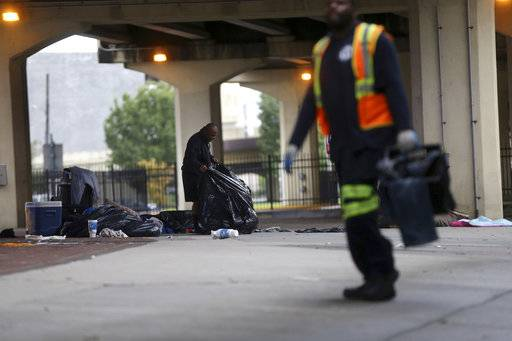 A homeless person, left, collects his belongings under the Pontchartrain Expressway, as sanitation employees carry people's possessions to a garbage truck, during a homeless sweep in New Orleans, in advance of approaching Hurricane Nate, Saturday, Oct. 7, 2017.