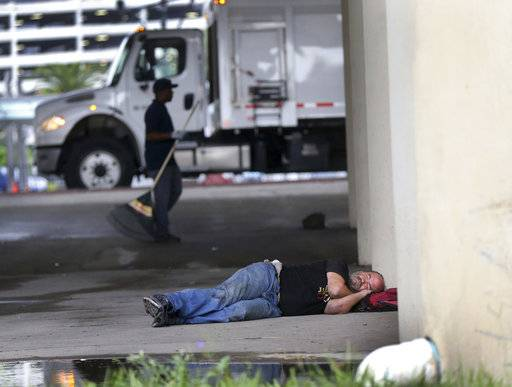 A homeless person, sleeps under the Pontchartrain Expressway, as sanitation employees perform a homeless sweep in New Orleans, in advance of approaching Hurricane Nate, Saturday, Oct. 7, 2017.