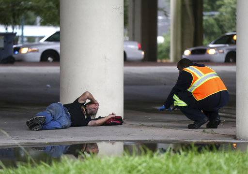 A sanitation employee, right, talks to a homeless person under the Pontchartrain Expressway, during a homeless sweep in New Orleans, in advance of approaching Hurricane Nate, Saturday, Oct. 7, 2017.