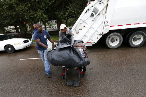 Sanitation employees, left, assist a homeless person with his belongings during a homeless sweep in New Orleans, in advance of approaching Hurricane Nate, Saturday, Oct. 7, 2017.