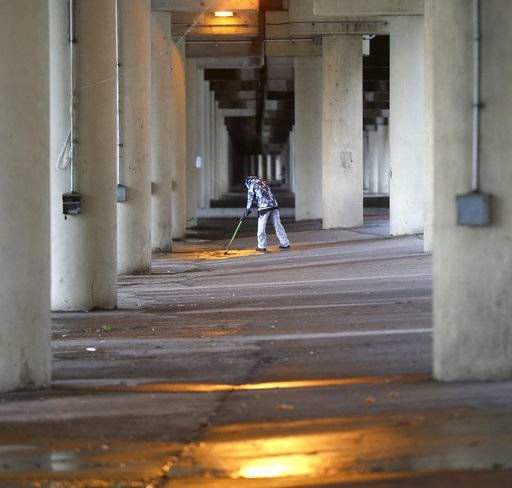 A homeless woman mops the area she was staying, as sanitation employees, not pictured perform a homeless sweep in New Orleans, in advance of approaching Hurricane Nate, Saturday, Oct. 7, 2017.