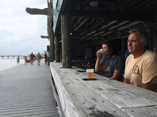 Ray Courterier and his daughter Alicia drink beer at a beachfront bar as Hurricane Nate approaches the Gulf coast in Pensacola Beach, Fla., on Saturday, Oct. 7, 2017. Coastal residents from Louisiana to the Florida panhandle braced for the effects of fast-moving Hurricane Nate, expected to hit sometime Saturday night.
