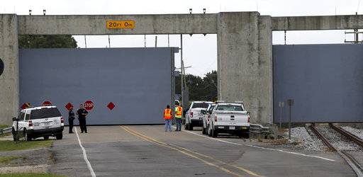 Workers close the floodgate separating St. Bernard Parish from the East Bank of Plaquemines Parish, in Violet, La., in preparation for Hurricane Nate, expected to make landfall on the Gulf Coast, Saturday, Oct. 7, 2017.