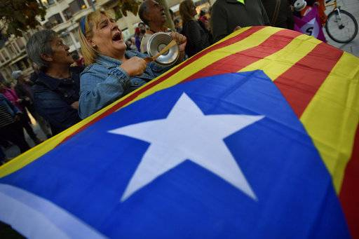 "Pro-independence supporters shout slogans in front of the Popular Party headquarters as a ""esteleda"" or  pro-independence flag is held up, in support of the Catalonia's secession, in Pamplona, northern Spain, Friday, Oct. 6, 2017."