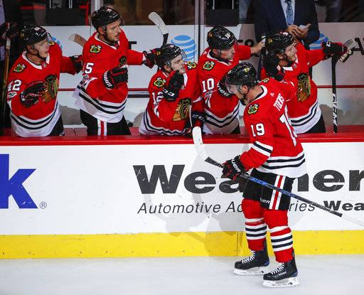 Chicago Blackhawks center Jonathan Toews (19) celebrates with teammates after scoring against the Columbus Blue Jackets during the second period of an NHL hockey game Saturday, Oct. 7, 2017, in Chicago.
