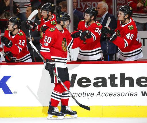 Chicago Blackhawks left wing Brandon Saad (20) celebrates with teammates after scoring against the Columbus Blue Jackets during the first period of an NHL hockey game Saturday, Oct. 7, 2017, in Chicago.