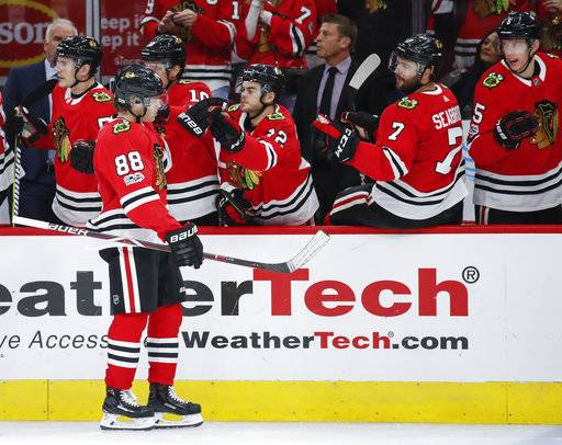 Chicago Blackhawks right wing Patrick Kane (88) celebrates with teammates after scoring against the Columbus Blue Jackets during the first period of an NHL hockey game Saturday, Oct. 7, 2017, in Chicago.