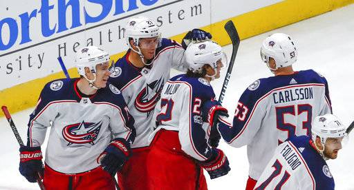 Columbus Blue Jackets left wing Sonny Milano, center, celebrates with teammates after scoring against the Chicago Blackhawks during the second period of an NHL hockey game Saturday, Oct. 7, 2017, in Chicago.