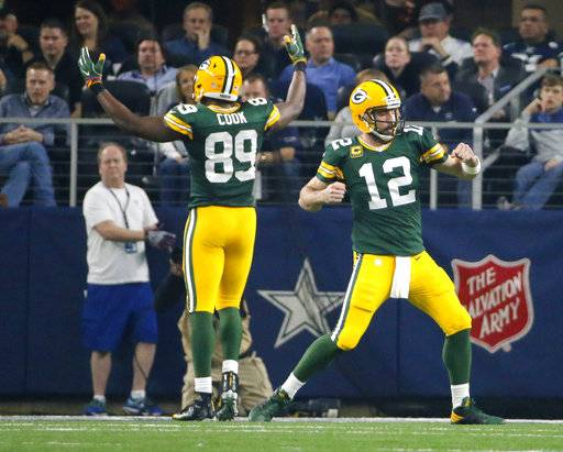 FILE - In this Jan. 15, 2017, file photo, Green Bay Packers' Aaron Rodgers (12) and Jared Cook (89) celebrate after a touchdown during the first half of an NFL divisional playoff football game against the Dallas Cowboys in Arlington, Texas. Packers-Cowboys has been one of the NFL's most entertaining and meaningful rivalries for decades. Whether it was the Ice Bowl or Rodgers' impromptu pass to Cook in the second half the playoff game, people (and players and coaches) remember these matchups. They'll be back at it on Sunday when Green Bay (3-1) visits Dallas (2-2).