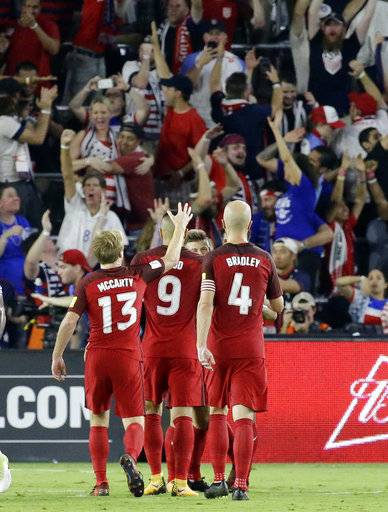 United States' Bobby Wood (9) celebrates his goal against Panama in front of cheering fans, with teammates Dax McCarty (13) and Michael Bradley (4) during the second half of a World Cup qualifying soccer match, Friday, Oct. 6, 2017, in Orlando, Fla. The United States won 4-0.