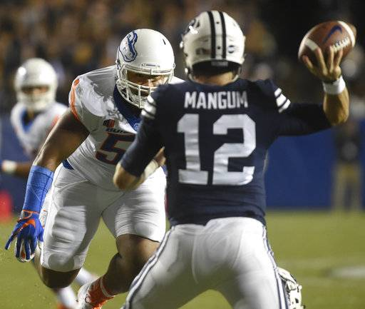 Boise State's Emmanuel Fesili closes in on BYU quarterback Tanner Mangum (12) during an NCAA college football game Friday, Oct. 6, 2017, in Provo, Utah. (Drew Nash/The Times-News via AP)