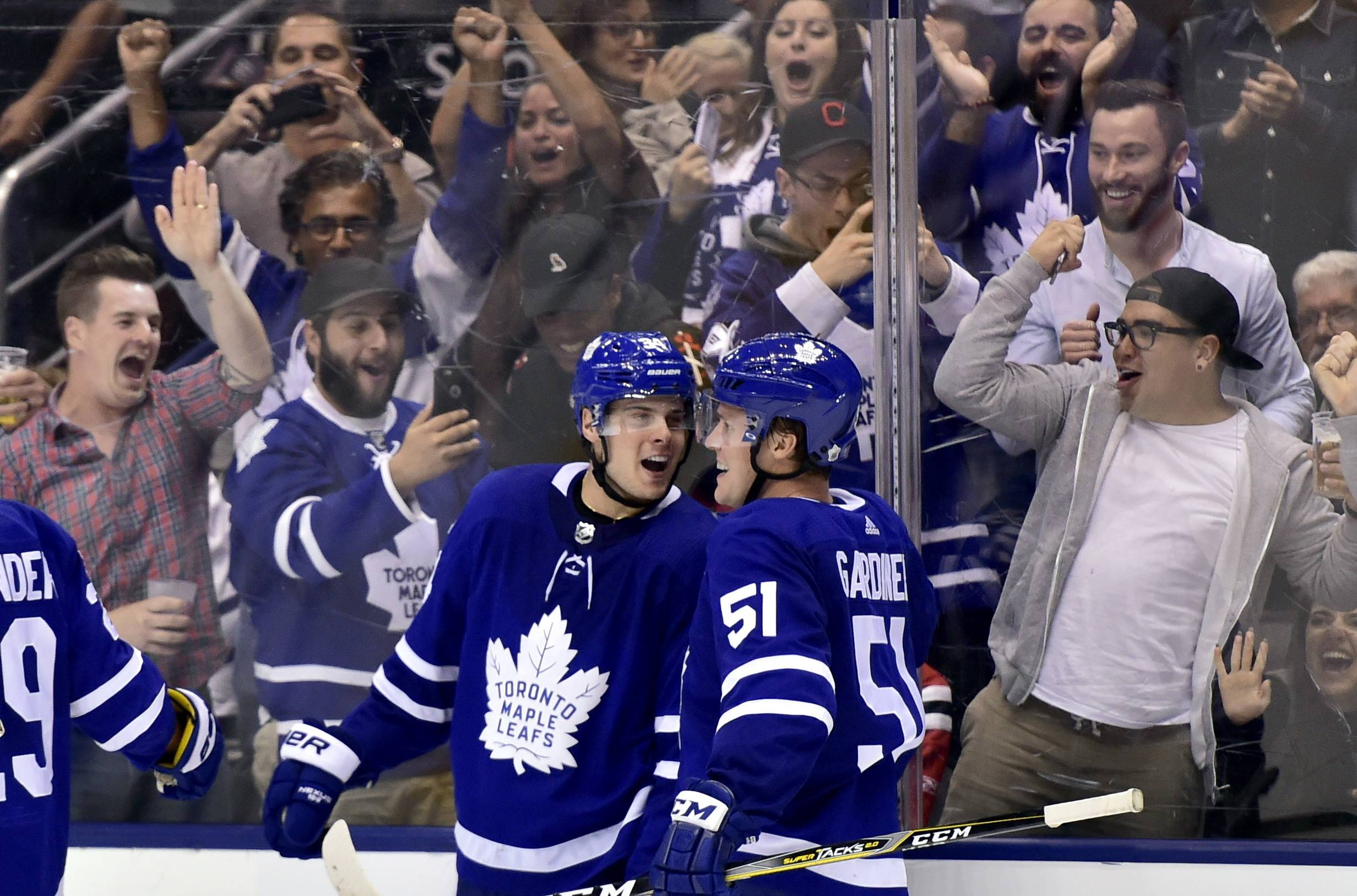 Toronto Maple Leafs center Auston Matthews (34) celebrates his game-winning goal with teammate Jake Gardiner (51) during overtime of an NHL hockey game against the Chicago Blackhawks in Toronto on Monday, Oct. 9, 2017.