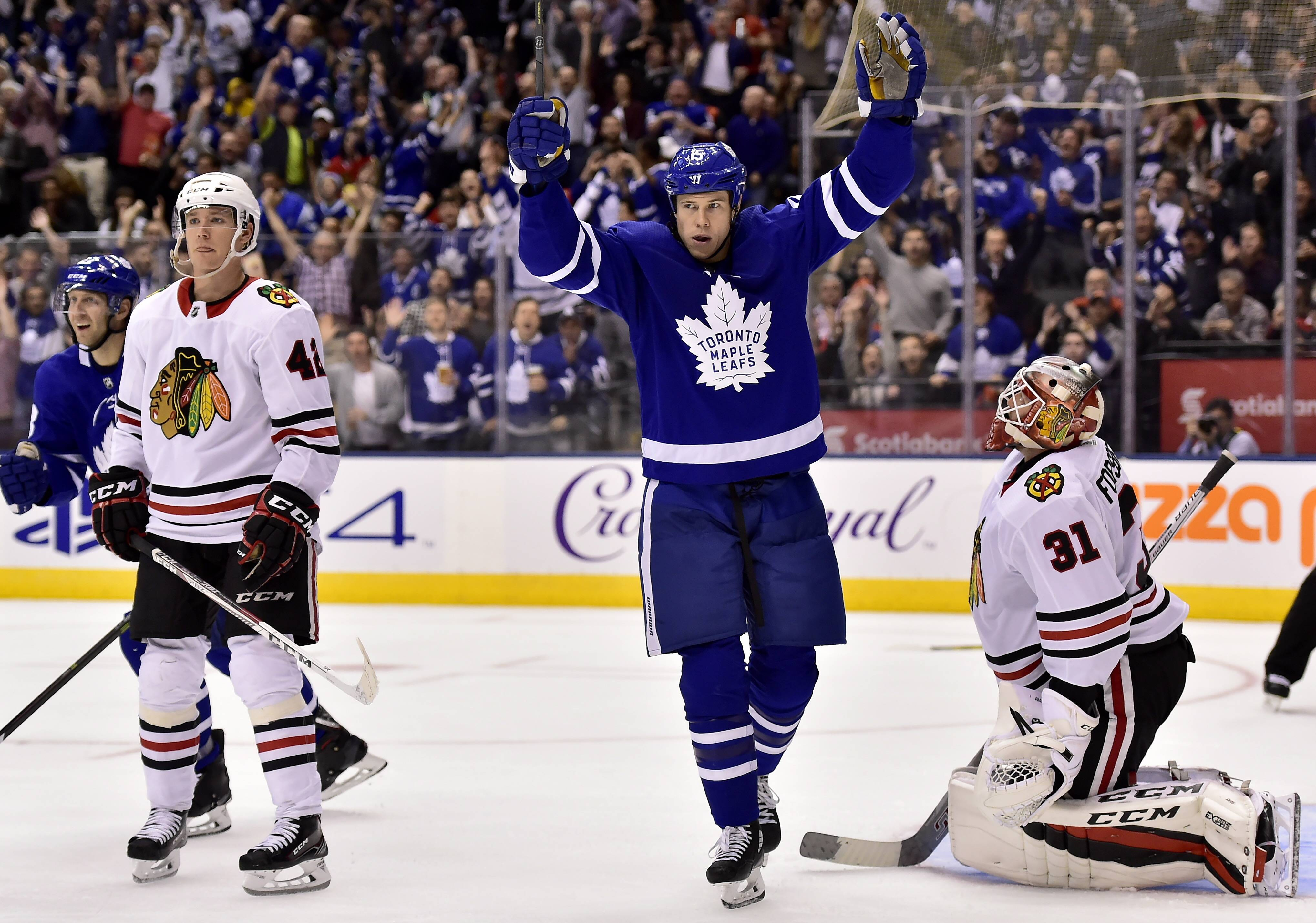 Toronto Maple Leafs left wing Matt Martin (15) celebrates a goal by teammate Nikita Zaitsev (22), not shown, as Chicago Blackhawks goalie Anton Forsberg (31) and teammate Gustav Forsling (42) look on during the second period of an NHL hockey game in Toronto on Monday, Oct. 9, 2017.