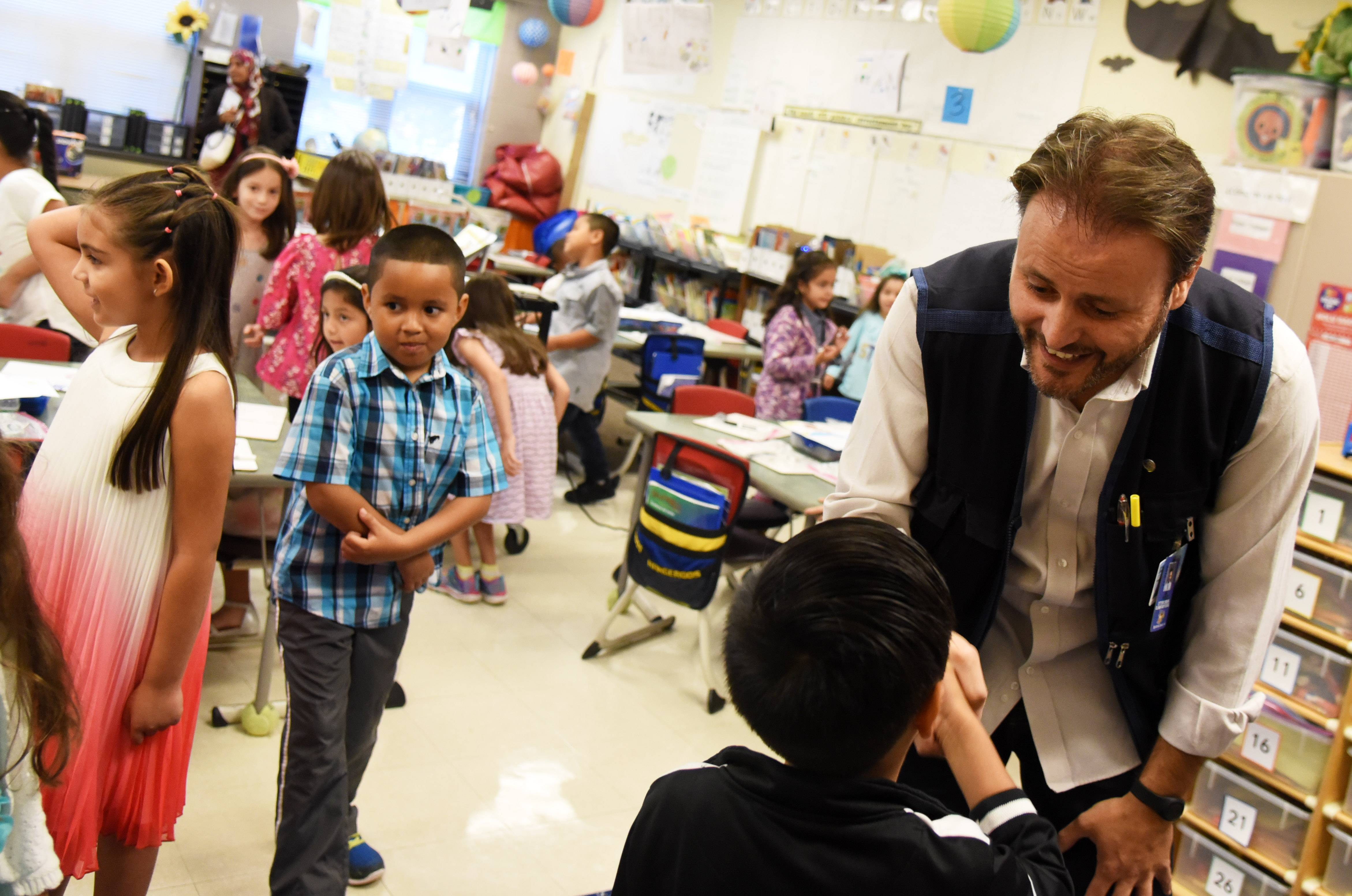 Juan Perez shows first-graders how to properly shake hands and look someone in the eye Thursday at Otter Creek Elementary School in Elgin. He helped establish the school's dual language program in 2011.