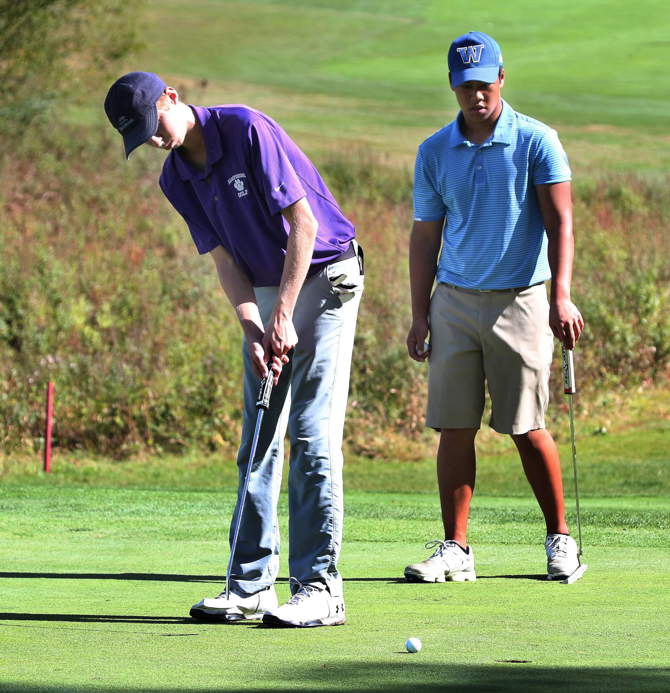 Hampshire's Mark Spitzer putts on the 18th hole as Warren's Karl Tolentino watches during the Class 3A Warren boys golf sectional on Monday at Bittersweet Golf Club in Gurnee.