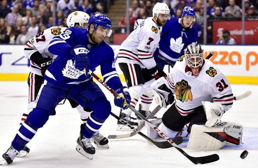 Chicago Blackhawks goalie Anton Forsberg (31) looks on as Toronto Maple Leafs center Nazem Kadri (43) chases the puck during the second period of an NHL hockey game in Toronto on Monday, Oct. 9, 2017. (Frank Gunn/The Canadian Press via AP)