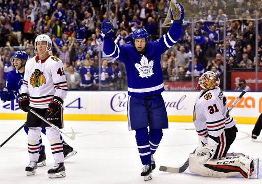 Toronto Maple Leafs left wing Matt Martin (15) celebrates a goal by teammate Nikita Zaitsev (22), not shown, as Chicago Blackhawks goalie Anton Forsberg (31) and teammate Gustav Forsling (42) look on during the second period of an NHL hockey game in Toronto on Monday, Oct. 9, 2017. (Frank Gunn/The Canadian Press via AP)