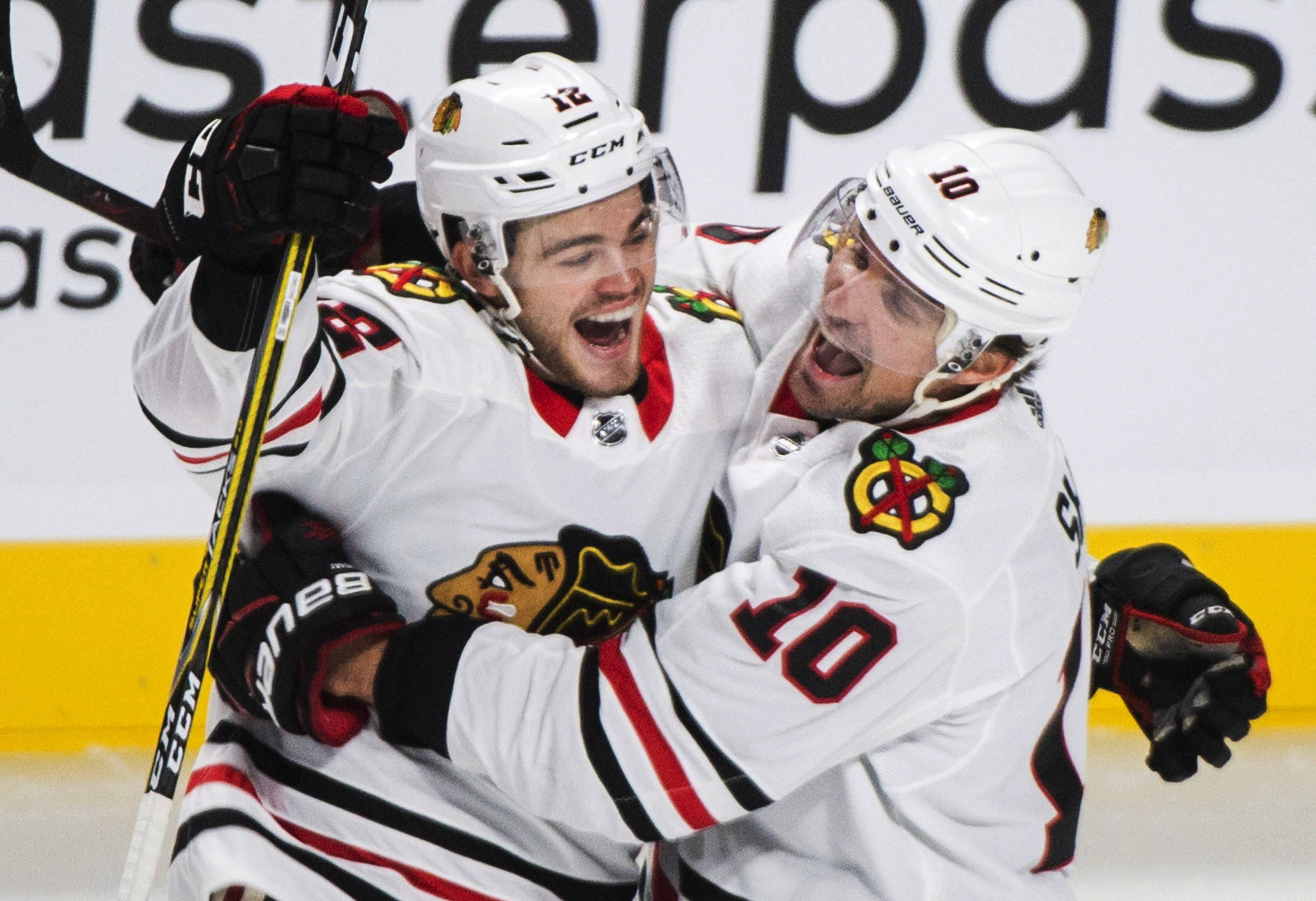 Chicago Blackhawks rookie Alex DeBrincat (12) celebrates with teammate Patrick Sharp after scoring against the Montreal Canadiens during the first period of an NHL hockey game in Montreal, Tuesday, Oct. 10, 2017.
