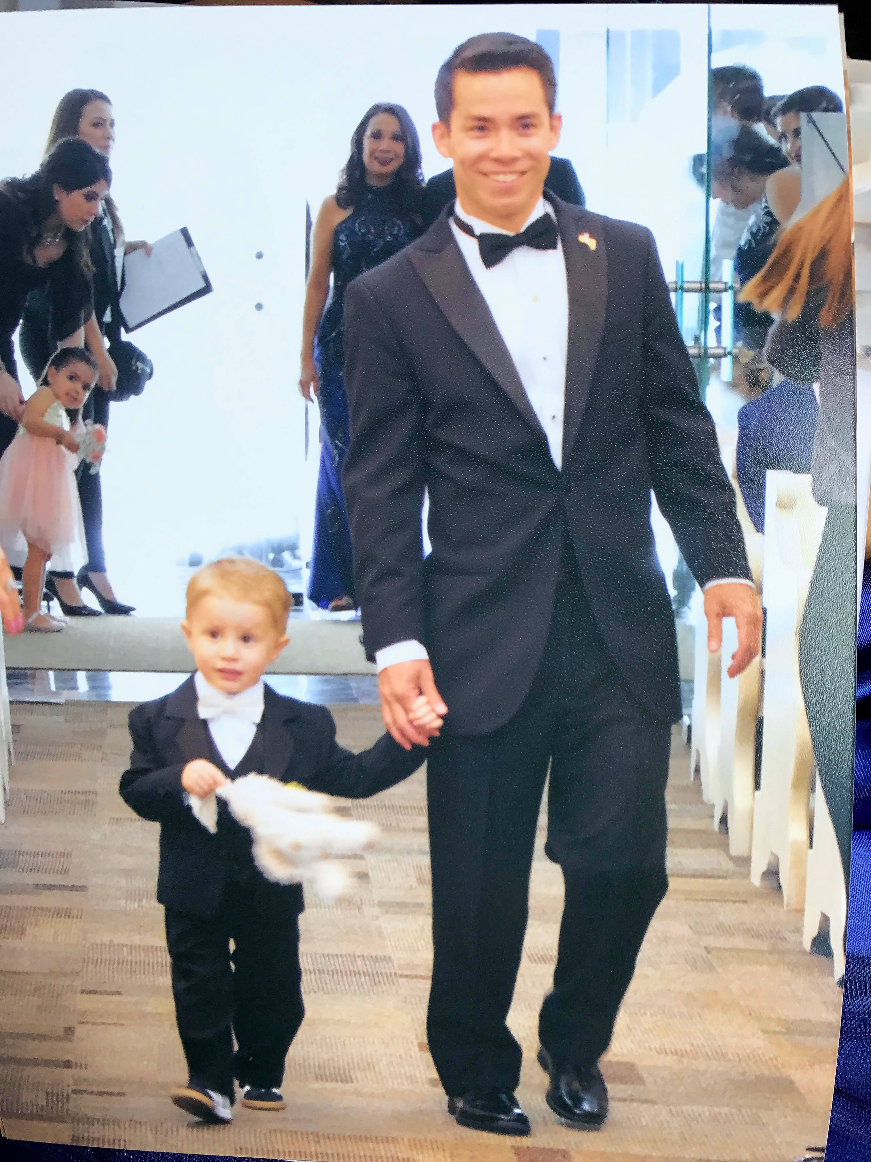 Dan Hohs walks down the aisle with a young family member during his brother's wedding in May.