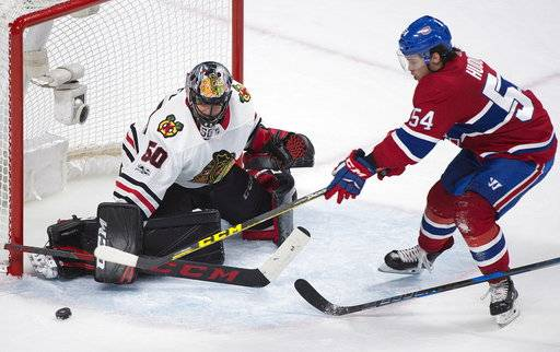 Chicago Blackhawks goalie Corey Crawford makes a save against Montreal Canadiens' Charles Hudon (54) during the third period of an NHL hockey game in Montreal, Tuesday, Oct. 10, 2017. (Graham Hughes/The Canadian Press via AP)