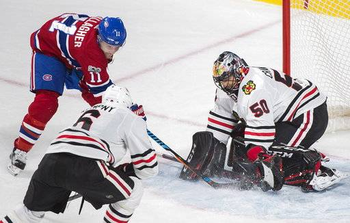 Chicago Blackhawks goalie Corey Crawford makes a save against Montreal Canadiens' Brendan Gallagher (11) as Blackhawks' Michal Kempny defends during the second period of an NHL hockey game in Montreal, Tuesday, Oct. 10, 2017. (Graham Hughes/The Canadian Press via AP)