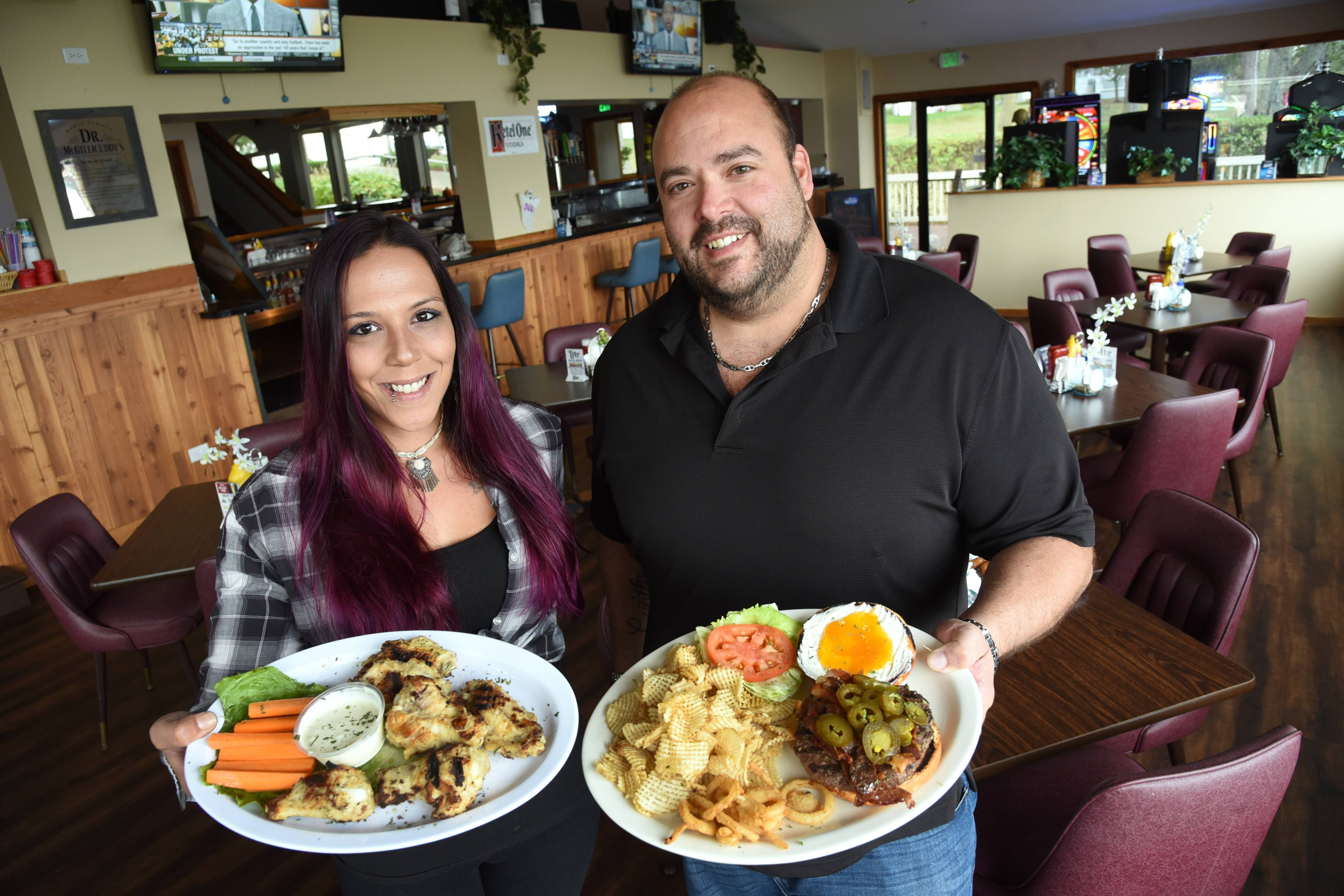Oasis on Bluff Lake assistant manager/bartender Amanda Cordero, left, shows off a plate of Grecian wings and owner Lou Buccelli touts the Oasis Burger at the Antioch restaurant.
