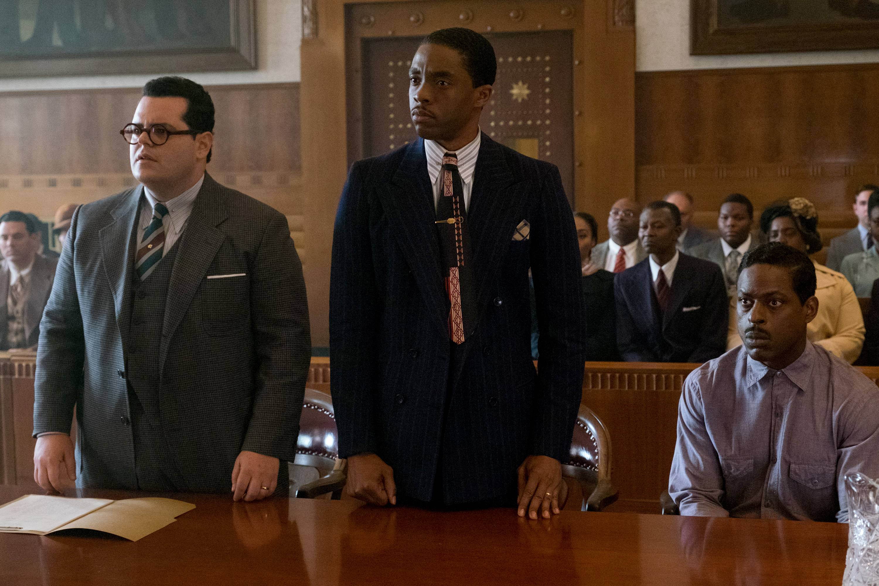 "A Jewish attorney (Josh Gad), left, and a NAACP lawyer (Chadwick Boseman) team up to defend a chauffeur (Sterling K. Brown), right, accused of rape and attempted murder in the fact-based drama ""Marshall."""