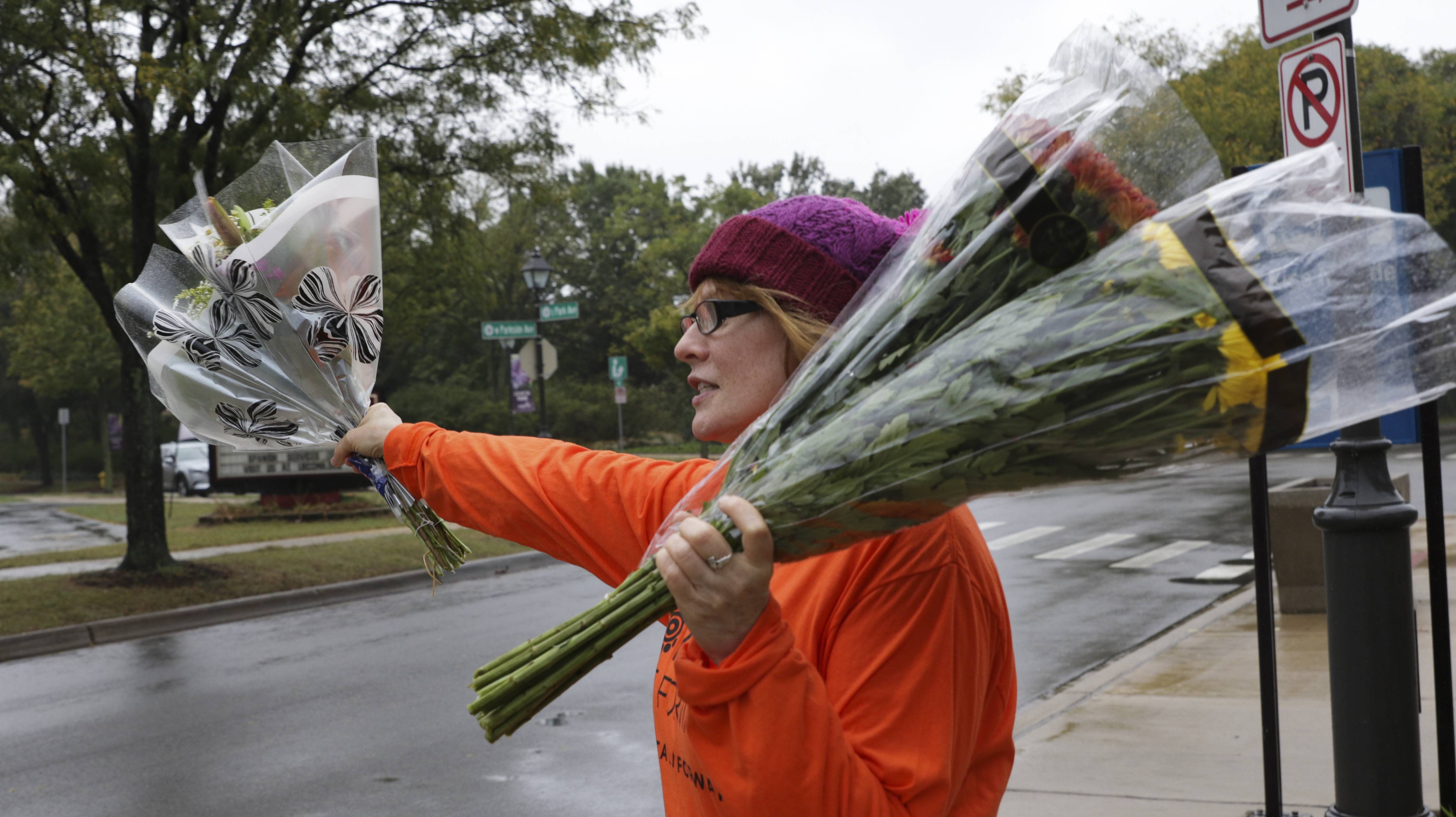 Lois Bafetti from Phillip's Flowers in Lombard hands out free bouquets Wednesday at the Lombard Metra station as part of a Petal It Forward campaign to spread happiness.