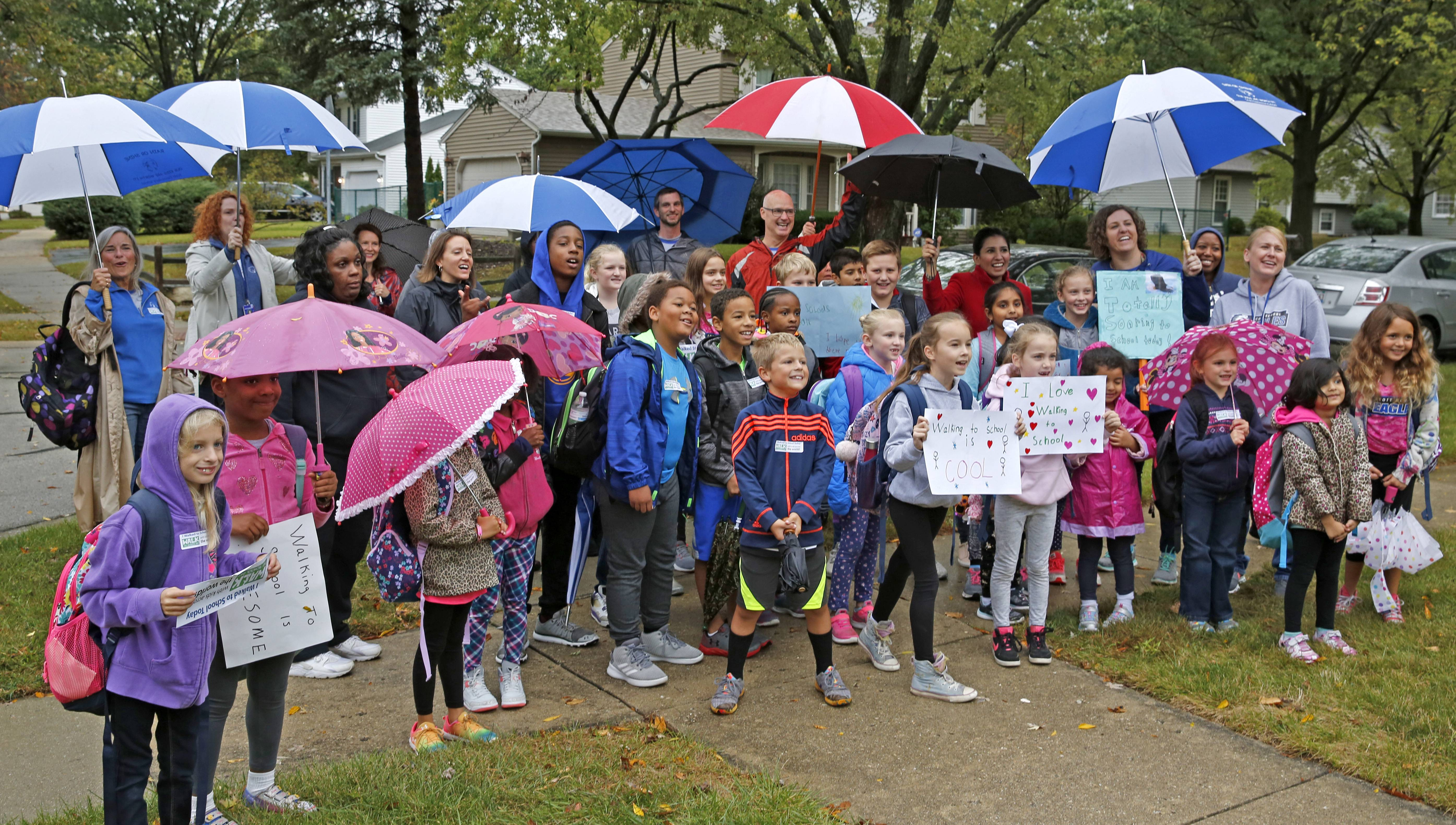 Students, parents and teachers prepare to walk from Coach Drive and Carriage Hill Road to Scott Elementary School in Naperville to celebrate National Walk to School Day. The occasion came a week late because of weather, but still fell on a rainy morning.