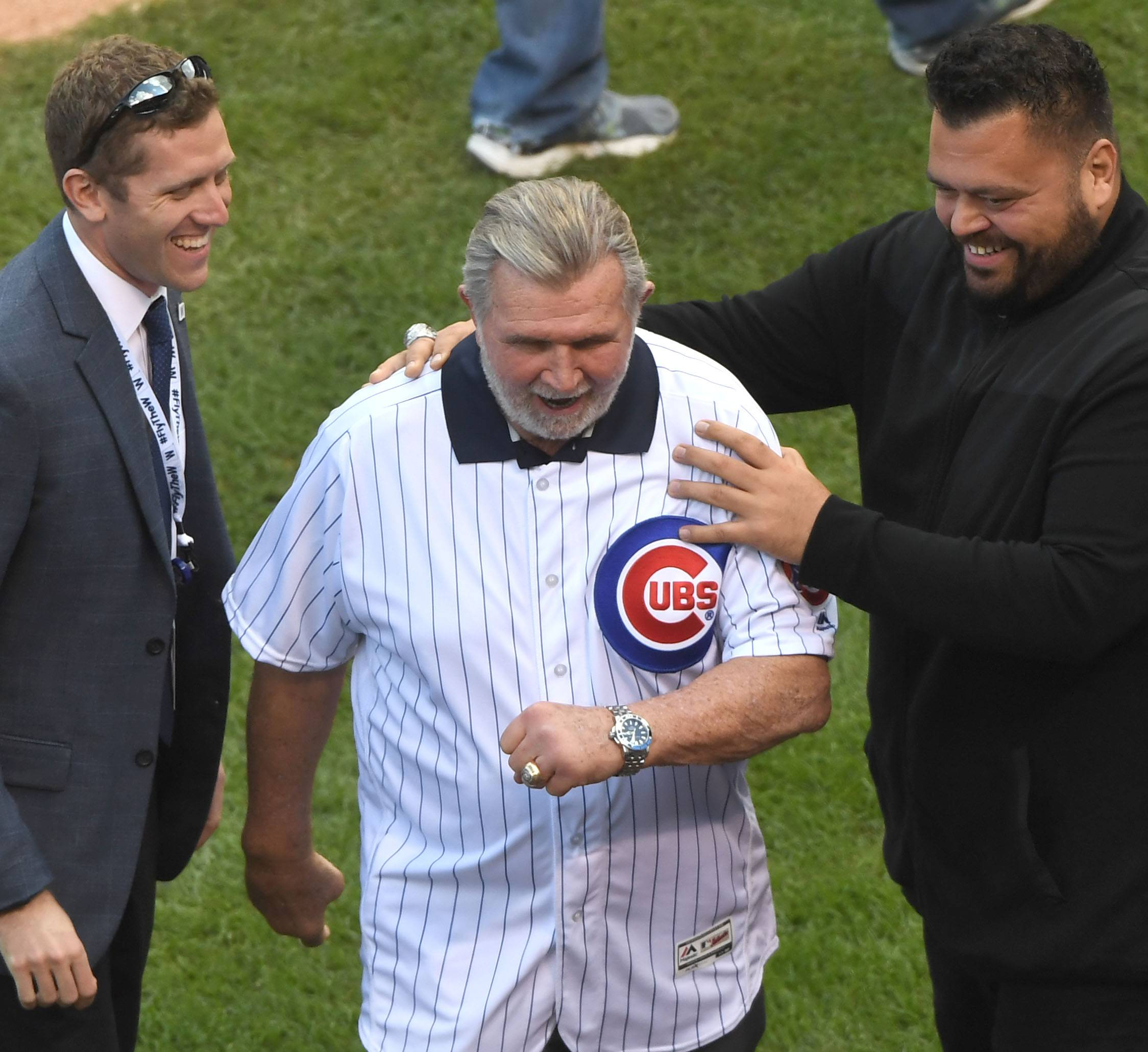 Mike Ditka, center, appears on the field before Game 3 of the NLDS at Wrigley Field in Chicago Monday.