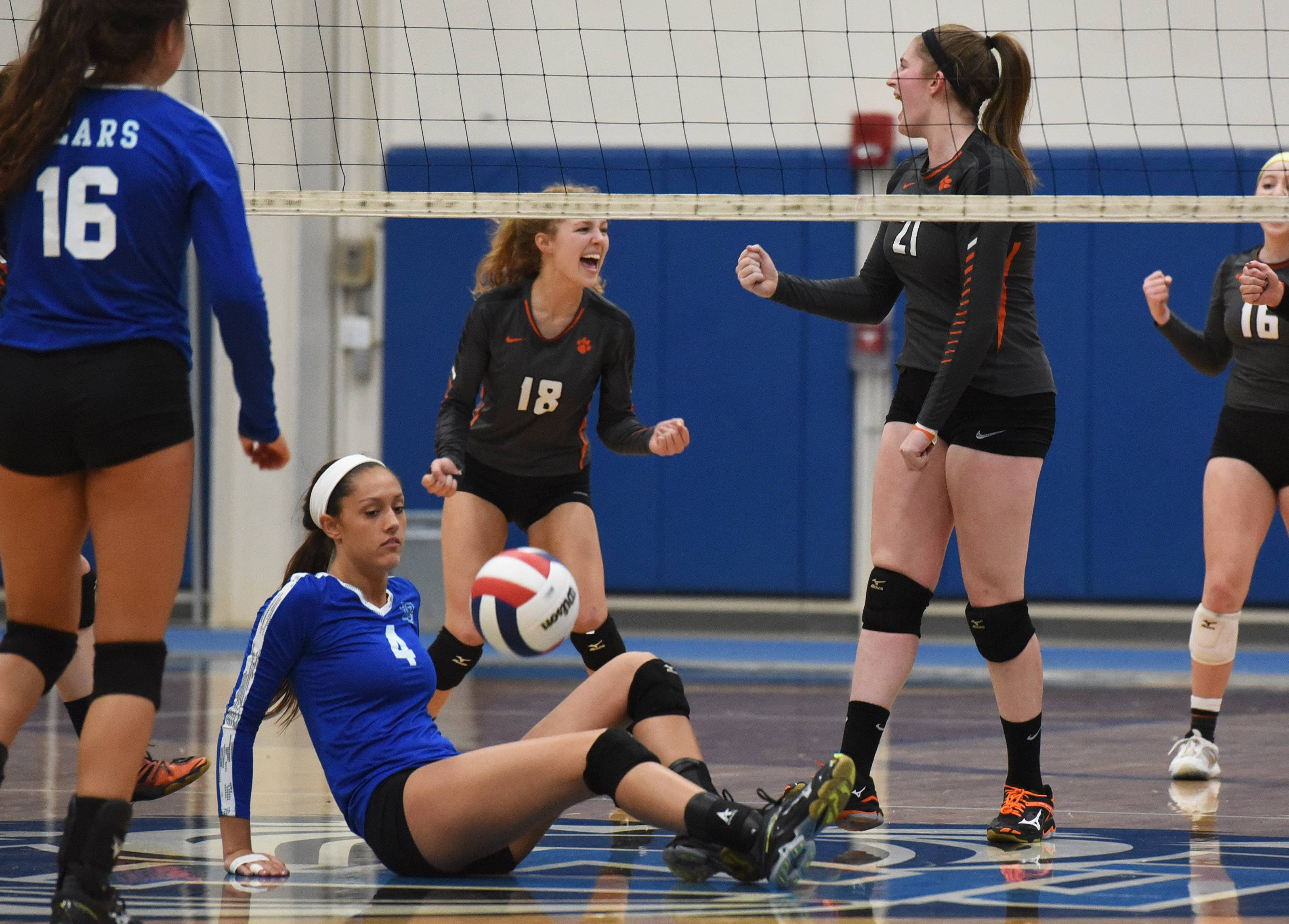 Lake Zurich's Jocelyn Leng (4) picks herself up as Libertyville's Cat Hebbeln (18) and Maggie Evers (21) celebrate a point during Wednesday's volleyball match in Lake Zurich.