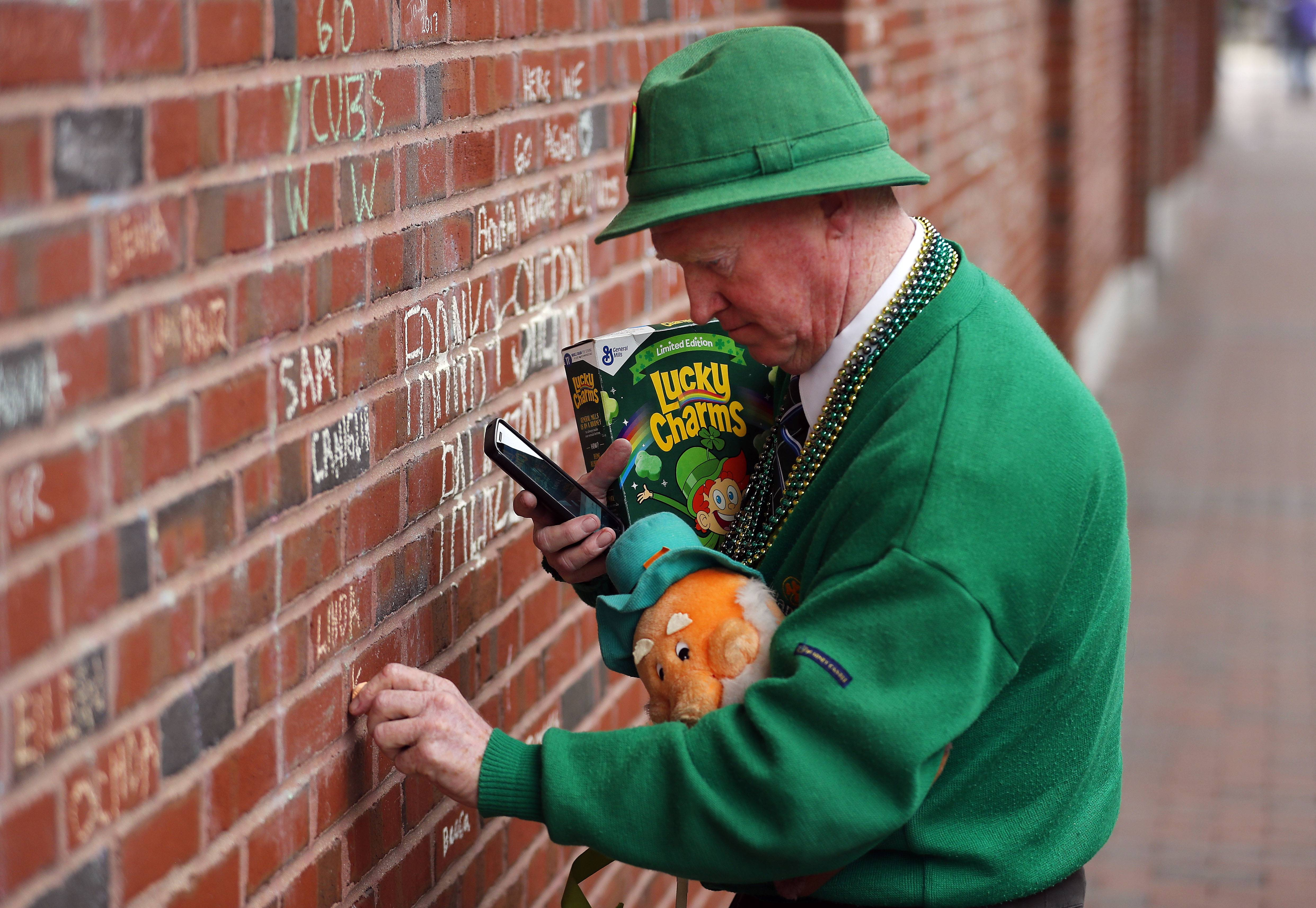 Tom McCarthy of Elgin uses chalk to write a note on the right field wall outside Wrigley Field.