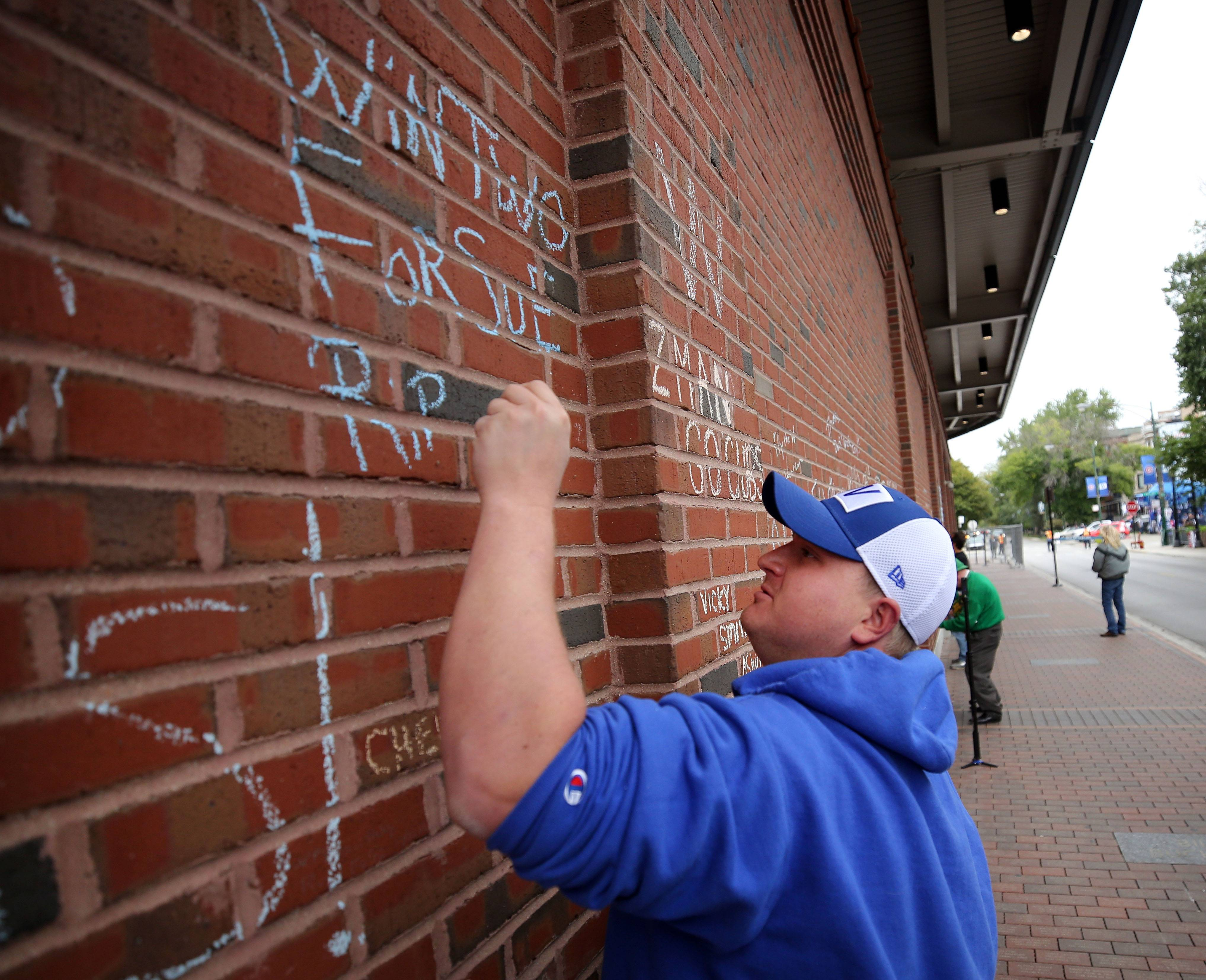 "Larry Scott of Glen Ellyn writes a note in chalk on Wrigley Field's right field wall for his grandmother, the ""biggest Cubs fan ever"" who died in September."