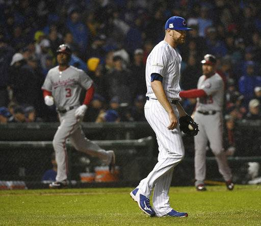 Chicago Cubs relief pitcher Wade Davis reacts as Washington Nationals' Michael Taylor rounds third base with a grand slam during Game 4 of a baseball National League Division Series at Wrigley Field in Chicago on Wednesday, Oct. 11, 2017. (John Starks/Daily Herald via AP)