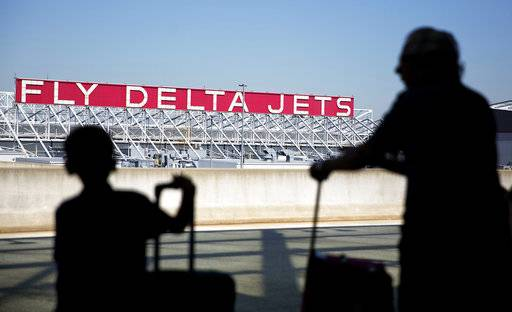 FILE - In this Thursday, Oct. 13, 2016, file photo, a Delta Air Lines sign overlooks the unloading area at Hartsfield-Jackson Atlanta International Airport, in Atlanta. Delta Air Lines, Inc. reports earnings, Wednesday, Oct. 11, 2017. (AP Photo/David Goldman, File)