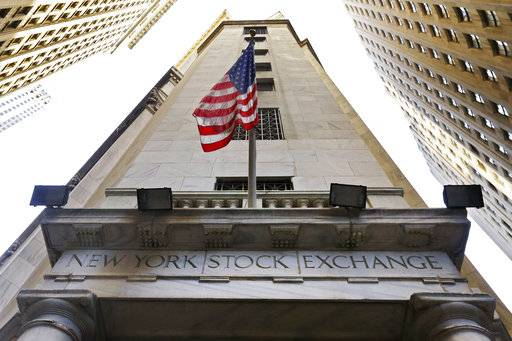 FILE - In this Friday, Nov. 13, 2015, file photo, the American flag flies above the Wall Street entrance to the New York Stock Exchange. U.S. stocks are mixed, Wednesday, Oct. 11, 2017, as household goods and health care companies move higher and banks and energy companies decline. (AP Photo/Richard Drew, File)