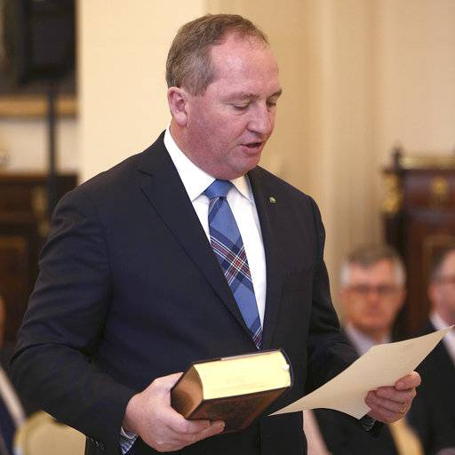 FILE - In this July 19, 2016, file photo, Australia's Deputy Prime Minister Barnaby Joyce takes the oath of office as he is sworn in at Government House in Canberra, Australia. Australia's constitutional ban on dual citizens becoming lawmakers is an unusual precaution against foreign interference in politics that critics have argued would eventually lead to problems in a multinational country with one of the highest immigration rates in the Western world. The High Court will be decide the fate of seven lawmakers that include Deputy Prime Minister Joyce. (AP Photo/Rob Griffith, File)