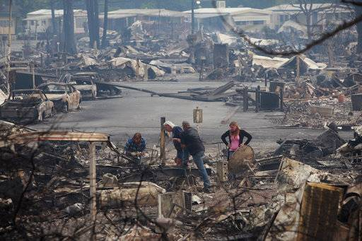 In this Monday, Oct. 9, 2017, photo, people salvage remains from Journey's End mobile parkin Santa Rosa, Calif. Officials say they have thousands of firefighters battling over a dozen blazes burning in Northern California and that more are coming from nearby states. (Karl Mondon/San Jose Mercury News via AP)