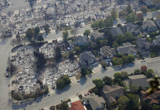 Burned out homes are seen next to homes that survived the flames of a massive wildfire in the Coffey Park area Wednesday, Oct. 11, 2017, in Santa Rosa, Calif. Wildfires whipped by powerful winds swept through Northern California sending residents on a headlong flight to safety through smoke and flames as homes burned. (AP Photo/Rich Pedroncelli)