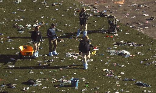 FILE - In this Oct. 3, 2017, file photo, investigators work among thousands of personal items at a festival grounds across the street from the Mandalay Bay Resort and Casino in Las Vegas. Friends and relatives of the victims and other concert-goers who survived returned Monday, Oct. 9, 2017, to reclaim baby strollers, shoes, phones, backpacks and purses left behind in the panic as they fled, at a Family Assistance Center at the Las Vegas Convention Center.