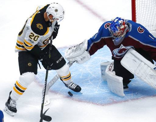 Boston Bruins center Riley Nash, left, tries to redirect a shot pasty Colorado Avalanche goalie Semyon Varlamov, of Russia, in the first period of an NHL hockey game Wednesday, Oct. 11, 2017, in Denver.
