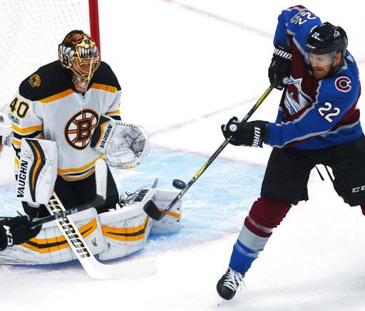 Boston Bruins goalie Tuukka Rask, left, of Finland, stops a redirected shot off the stick of Colorado Avalanche center Colin Wilson in the first period of an NHL hockey game Wednesday, Oct. 11, 2017, in Denver.