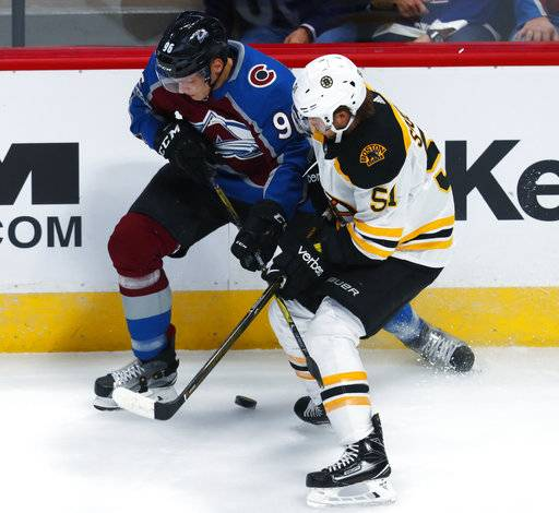 Colorado Avalanche right wing Mikko Rantanen, of Finland, left, tangles with Boston Bruins center Ryan Spooner for control of the puck in the first period of an NHL hockey game Wednesday, Oct. 11, 2017, in Denver.