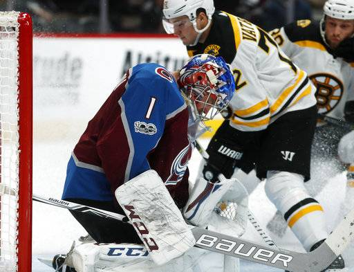 Colorado Avalanche goalie Semyon Varlamov, front, of Russia, makes a pad save of a redirected shot off the stick of Boston Bruins center Frank Vatrano in the second period of an NHL hockey game Wednesday, Oct. 11, 2017, in Denver.