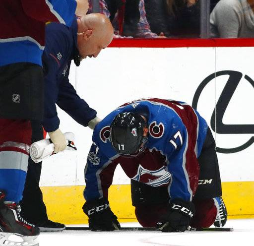 Colorado Avalanche center Tyson Jost, right, is attended to by trainer Matt Sokolowski after Jost was injured on a hit by Boston Bruins defenseman Adam McQuaid during the second period of an NHL hockey game Wednesday, Oct. 11, 2017, in Denver.
