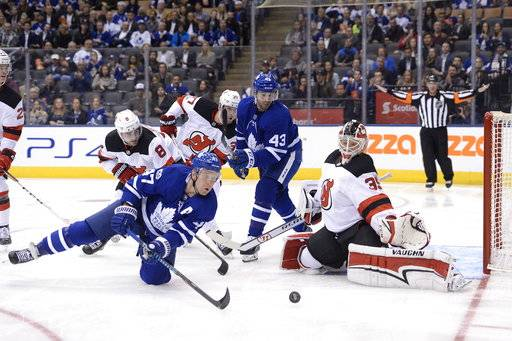 New Jersey Devils goalie Cory Schneider (35) makes a save as Toronto Maple Leafs' Leo Komarov (47) and Nazem Kadri (43) look for a rebound while Devils' Will Butcher (8) and Pavel Zacha (37) defend during the second period of an NHL hockey game Wednesday, Oct. 11, 2017, in Toronto. (Nathan Denette/The Canadian Press via AP)